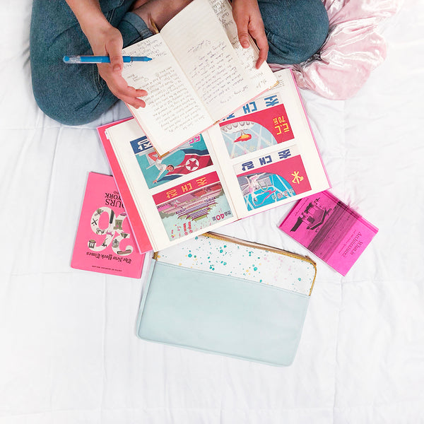 Girl writing in a journal surrounded by books, magazines, and a powder blue splatter laptop sleeve.