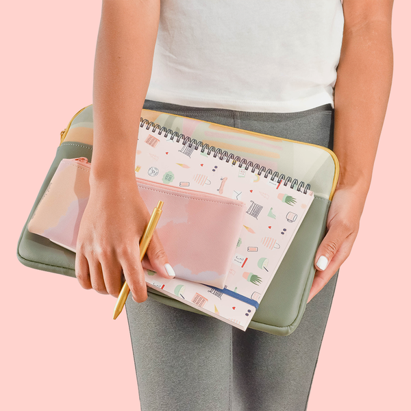 A woman holding a laptop sleeve, notebook and pencil pouch with a gold pen in her hand.