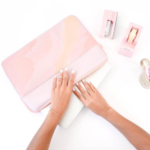 Girl's hand reaching into a Daydream laptop sleeve surrounded by a pink desk set.