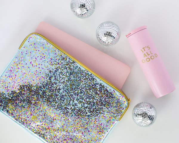 A confetti laptop sleeve sits with pink laptop and pink thermal drink ware.