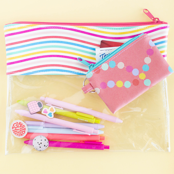 A pouch with clear vinyl and rainbow wavy line vegan leather.  There are jotter pens and enamel pins in the pouch. There is a coral colored penny pouch with a drivers license and credit card sticking out of it.