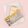 Cute pencil pouch in clear vinyl with glitter confetti, a slim design, and gold zipper on top of a macbook