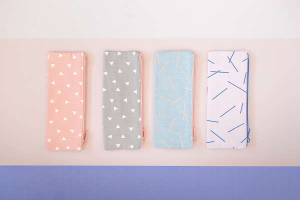 Four pouches sit on a surface. One with peach canvas material and white triangles. The second a grey background with white triangles. The third is a washed out denim with pink marks, and the fourth pouch is a light pink with navy marks.