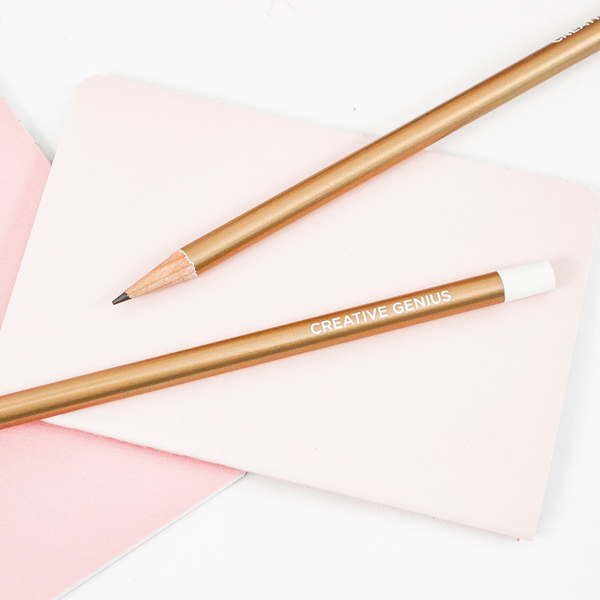 "Two gold pencils with the text ""Creative Genius"", laying on a white and pink surface"