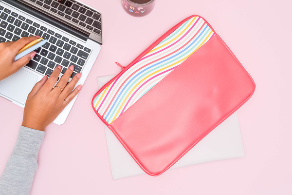 A laptop sleeve sits on a pink background while a woman works on a laptop.