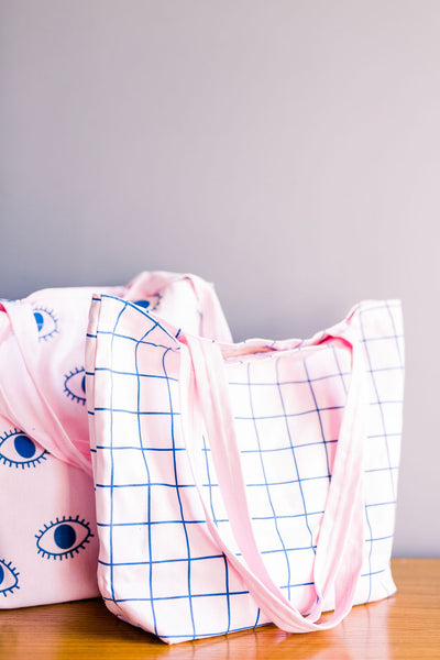 Two cute pink tote bags sitting on a table one with a grid pattern and one with eyeballs pattern.