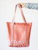 Girl's hand holding a cute tote bag in red with pink speckled pattern.