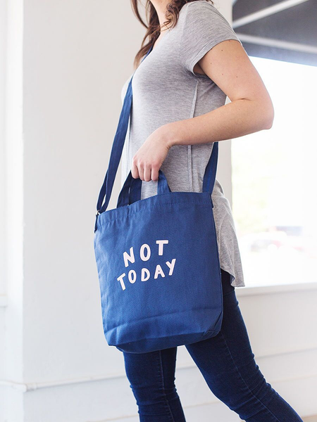Girl wearing a cute crossbody tote in navy blue canvas with Not Today design..