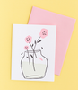 White greeting card with a flower vase containing three pink flowers.