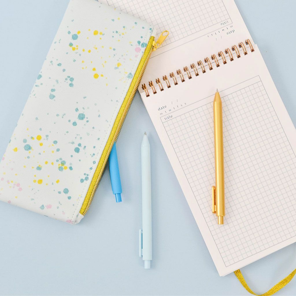 Cute pencil pouch in paint splatter print and a gold zippered top next to a task pad and three jotter pens