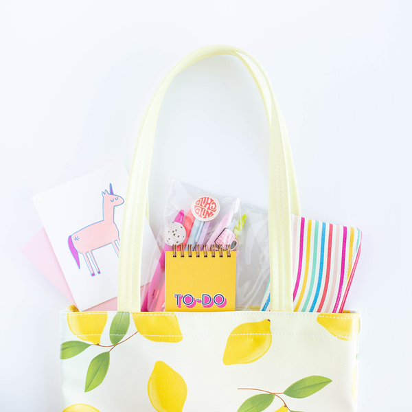 Cute tote bag with pastel background and yellow lemons pattern with various toot products inside