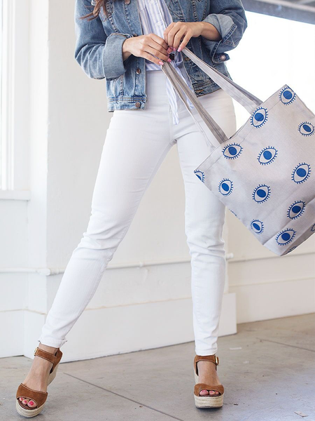 Woman in white jeans swinging a canvas tote bag in light gray with eyeballs pattern.