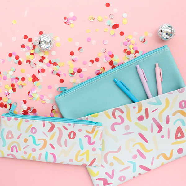 A small pencil pouch and a large pencil pouch with jotter pens, rainbow confetti, and small disco balls.