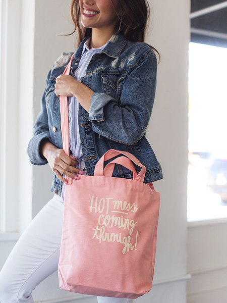 Smiling brunette girl wearing a cute crossbody tote in peach canvas with Hot Mess Coming Through design..
