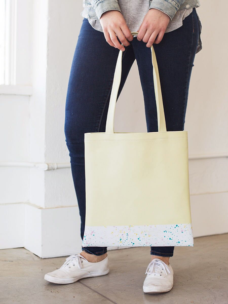Girl standing in jeans and white sneakers holding a yellow tote bag with white paint splatter detail along the bottom.