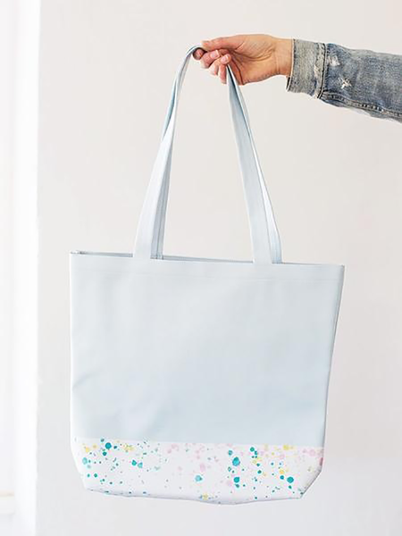 Girls hand holding a cute tote bag in powder blue with a white paint splatter detail along the bottom.