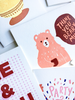An assortment of white greeting cards partially cropped. The main card has a peach colored bear holding a red mug. There is a text bubble with