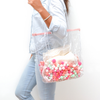 a girl holding Cute tote bag in clear vinyl with colorful pom poms and a peach zippered top.