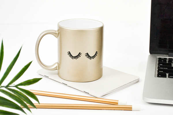 Funny coffee mug in metallic gold with two thick black eyelashes on the front next to a macbook and gold pencils