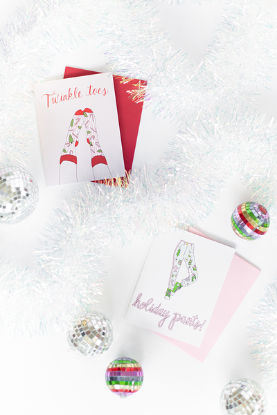 "Two greeting cards. The one of the upper left is white with the text ""Twinkle toes"" and feet wearing a pair of red, white and green holiday decorated socks. The card on the lower right is white with a light pink and green pair of holiday graphic decorated pants with script text ""holiday pants!"" below."
