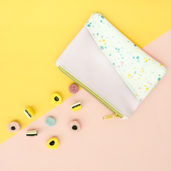 Pink and paint splatter pouch with gold zipper and tiny candies spilling out on a yellow and pink background.