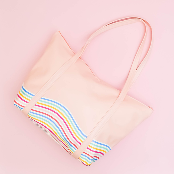 Weekender bag is laid on a pink surface, with it's straps raised above the zipper and the rainbow patters clearly visible.