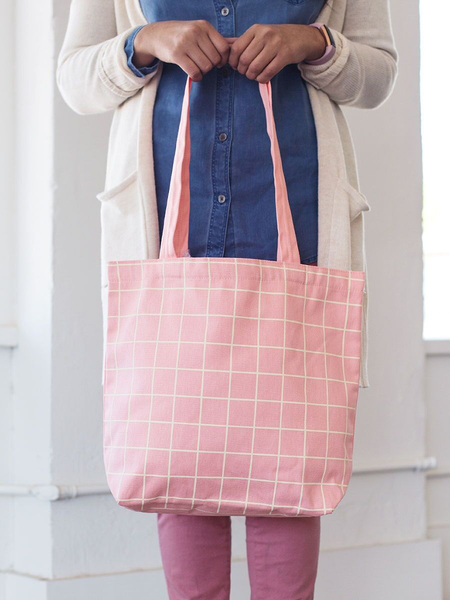 Girl holding a cute tote bag in peach canvas with yellow grid pattern.
