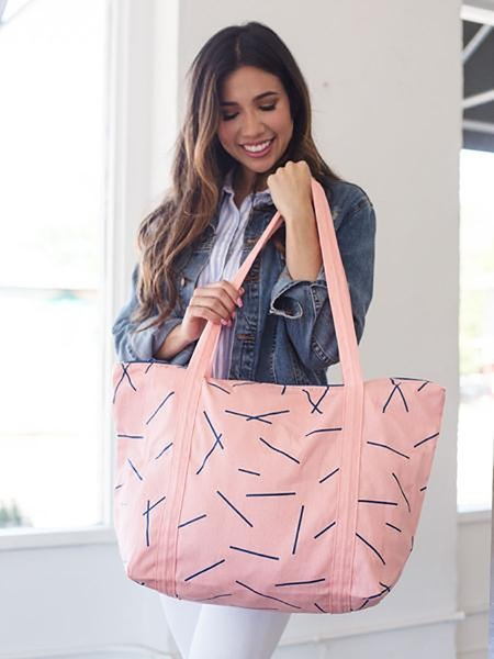 Brunette girl holding a cute tote bag in pink canvas with navy pixie sticks and double shoulder strap.