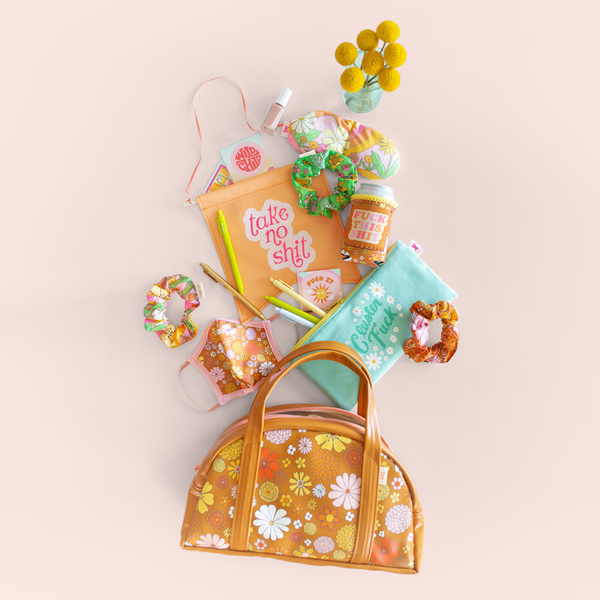 "group of flowered gift items spilling out of a floral bag with sayings ""take no shit"", ""cluster fuck"" and ""fuck this shit"""