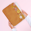 girls hand pulling laptop out of brown vegan leather laptop sleeve trimmed with fun floral print at the top with peach zipper