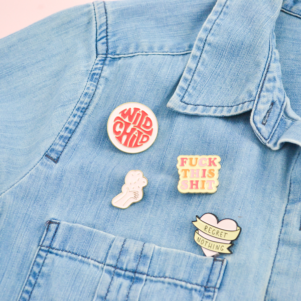 Our cute enamel pins pinned to a chambray denim shirt. Wild child, fuck this shit, so many feelings, and our confetti hand are the pins used in this picture.
