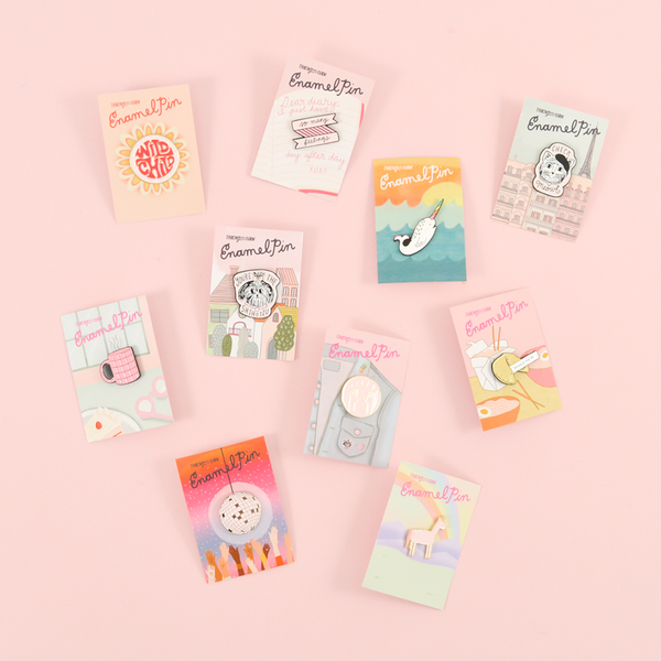 Several of our cute enamel pins on a pink background