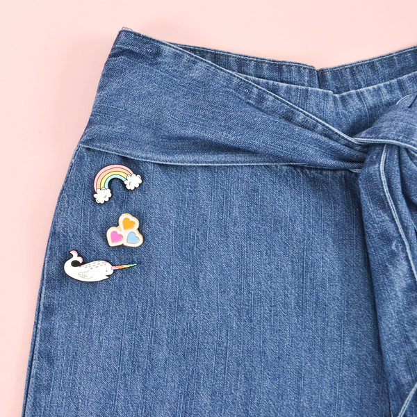 Our rainbow, hearts, and narwhal enamel pins pinned to a denim pair of jeans.
