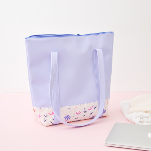 A periwinkle tote bag with magic sprigs on the bottom sitting next to a macbook