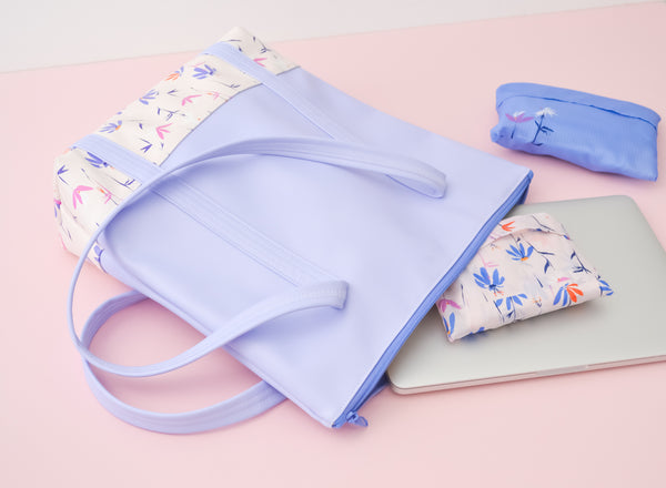 A periwinkle tote bag with magic sprigs on the bottom next to a macbook, and two packing cubes