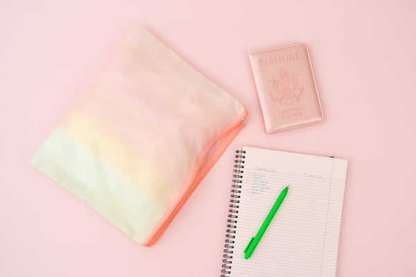 a ripstop pastel gradient pouch next to a notebook, green grass jotter, and a rose gold passport holder