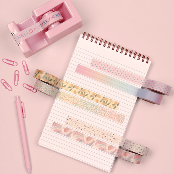 A notebook on a pink table with a pink tape dispenser, pens and paper clips. On the notebook six different washi take designs are taped onto the notebook page.