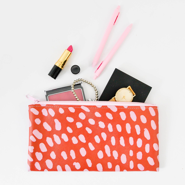 A cute pencil pouch in red with pink dots has lipstick, a phone, pens, and a watch spilling out.