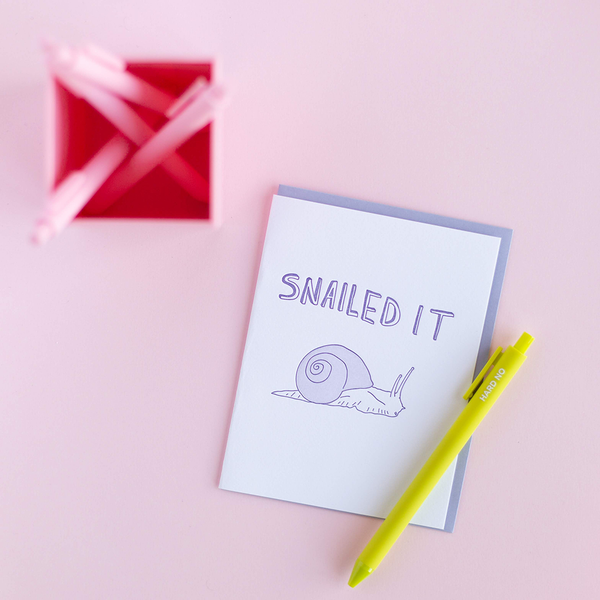 "White greeting card with a purple snail and purple text ""Snailed It'. There is a citron jotter pen with the text ""Hard No"" and a blush pink pen cup containing matching pens. The background is light pink."