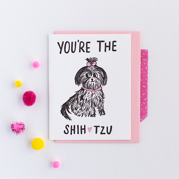 "White greeting card with black text ""Your're The Shih [pink heart graphic] tzu"". There is a drawing of a shih tzu dog with a pink color and a pink bow on it's head. There is a pink envelope and colorful poms in the background."