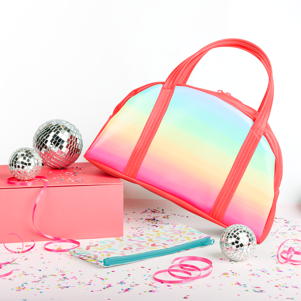 Rainbow handbag surrounded by disco balls and confetti.