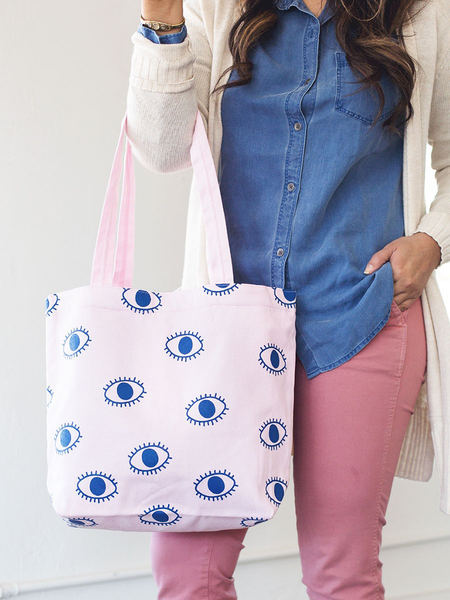 Brunette girl holding a pink canvas tote bag with eyeball pattern.