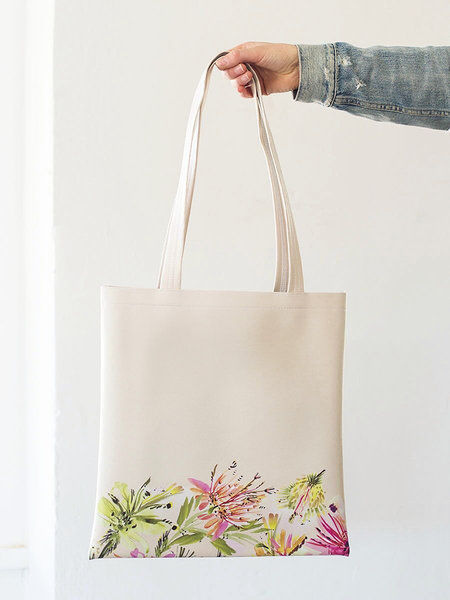 Woman's denim clad arm holding a most cream colored tropical mess main squeeze tote. The design has a multi colored floral print at the bottom.