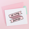 White greeting card with a pink and black banner and scripted writing