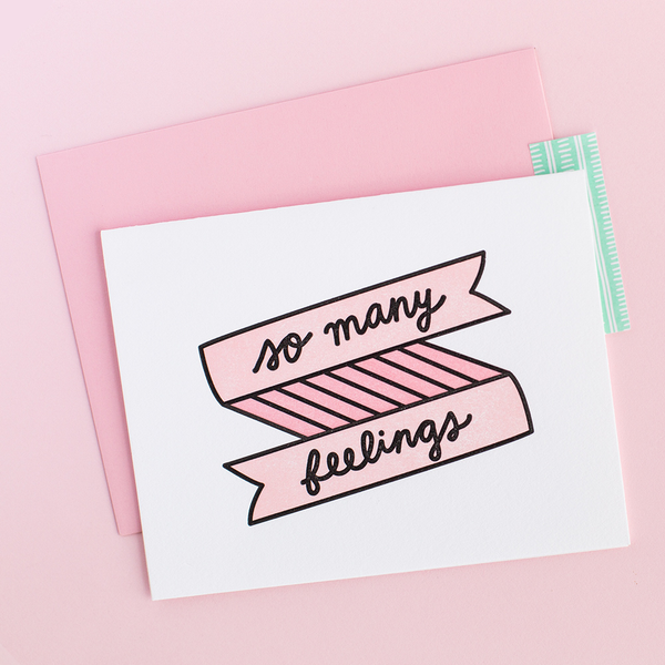 "White greeting card with a pink and black banner and scripted writing ""so many feelings"". There is a pink envelope and a pink background."