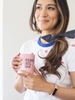 Smiling young woman looking off camera and holding a pink mug in front of her with both hands.