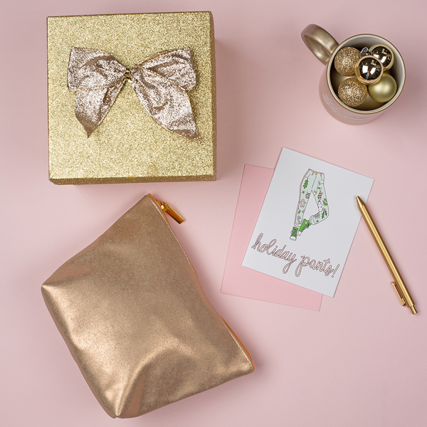 "A white greeting card with light green, medium green and pink pants decorated with holiday graphics. The script text at the bottom is ""holiday pants!"". There is a glittery gold gift box with a bow, a metallic gold zipper pouch, a metallic gold mug with gold ornaments and a gold jotter pen. The background is light pink."