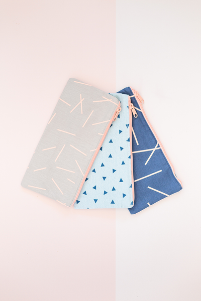 three different canvas pouches. one gray canvas with pixie sticks, one beach-washed denim with triangles, one navy with pixie sticks