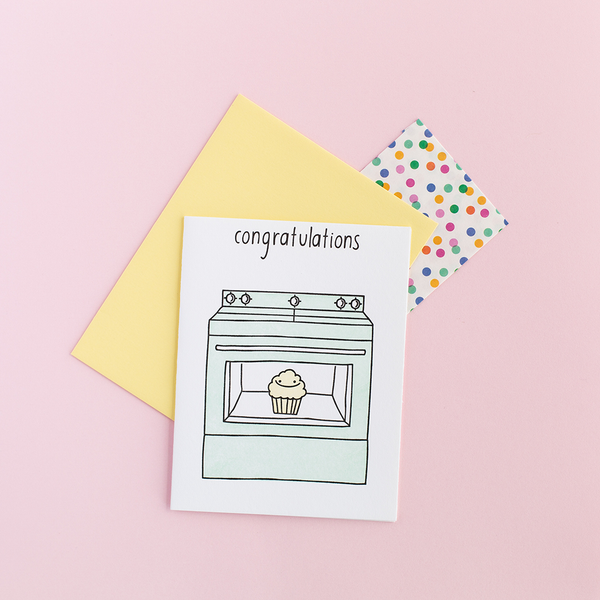 "White greeting card with a mint oven. The oven has a clear window with a smiling muffin in it. The text at the top is ""congratulations"". There is a yellow envelope and a small color polka dot gift bag against a pink background."