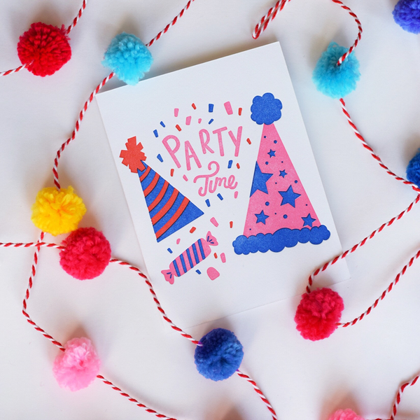 "A white greeting card with a red and blue striped party hat, a pink with blue stars party hat and a pink and white wrapped piece of candy. There is red, blue and pink confetti with the text ""Party Time""."